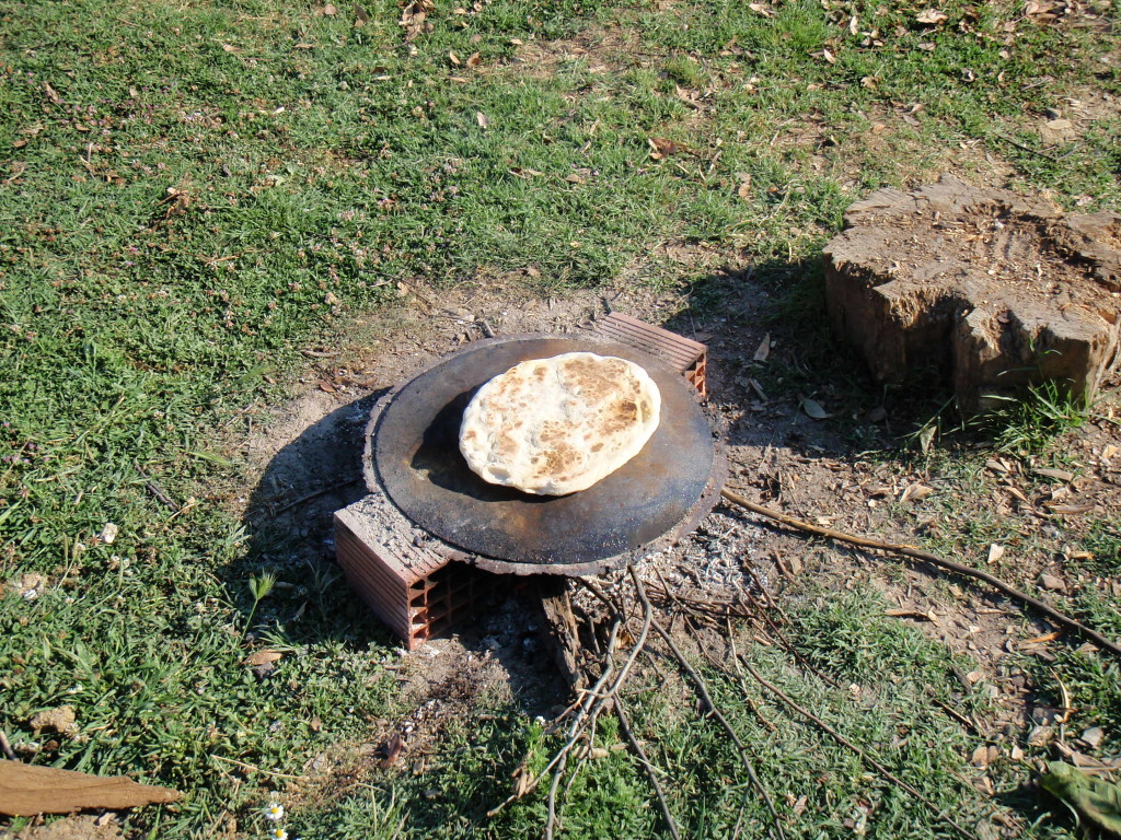 Baking bread on an open fire with a steel plate.