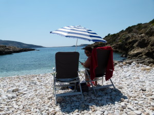 Jenny and our new beach umbrella overlooking a small bay with a pebble beach.