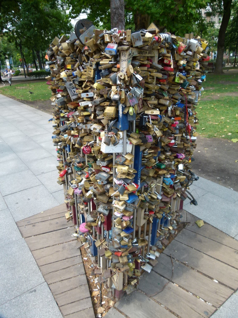 a locksmiths dream, padlocks that pledge love on a metal tree protector