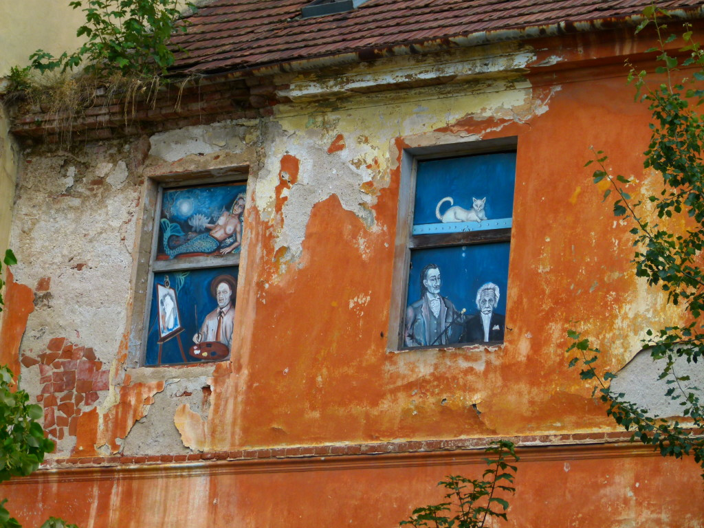 A derelict building with some artwork in the windows.