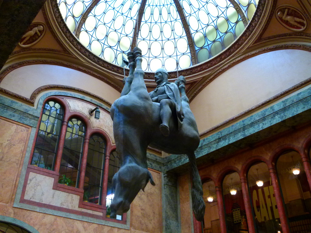 Hanging from the ceiling of the Art Nouveau Lucerna Palace in Prague, an ancient king rides triumphantly astride... an upside-down, apparently dead horse. Created by Prague-born artist David Cerny.