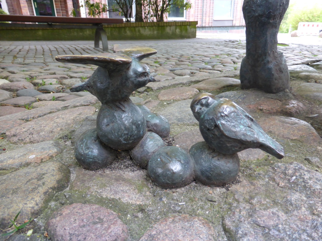 Birds are sitting on the house dung at the back of the statue.
