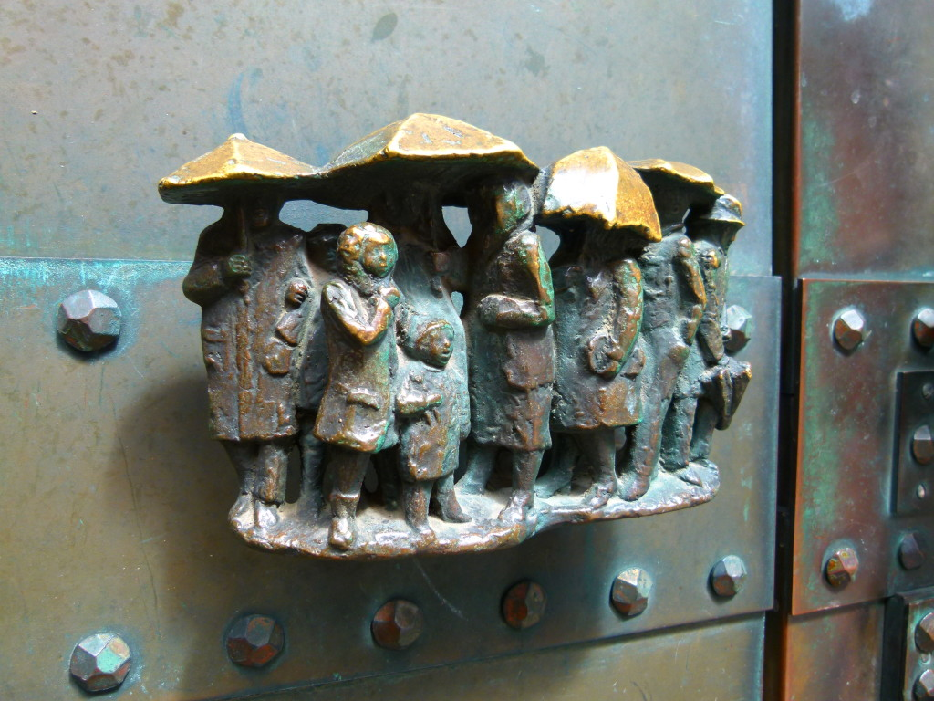 Door handle at the side of the church. Little people in the rain.