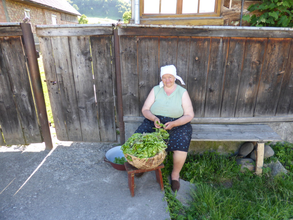 Preparing vegetables out the front of her house. Watching the world go by .